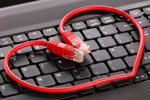 Red data cable wrapped in the shape of a heart, on keyboard, symbolizing internet dating