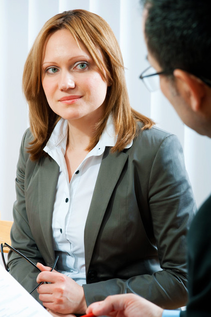Business woman looking guardedly at the gentleman she is listening to.